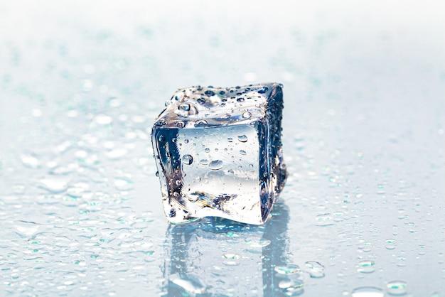 Cubo de gelo derretendo na mesa molhada