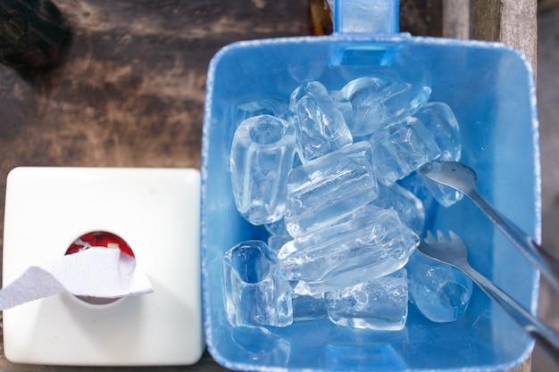 Cubo de gelo na cesta plástica azul. estilo tailandês do serviço do restaurante.
