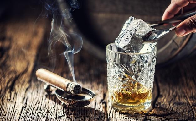 Cubo de gelo sendo colocado em um copo ornamental de uísque colocado em uma madeira antiquada e queimando charuto à parte.