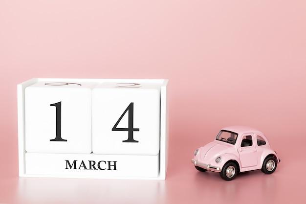 Cubo de madeira 14 de março. dia 14 de março mês, calendário em um fundo rosa com carro retrô.