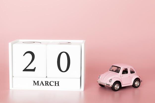 Cubo de madeira 20 de março. dia 20 de março mês, calendário em um fundo rosa com carro retrô.