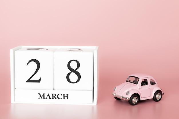 Cubo de madeira 28 de março. dia 28 do mês de março, calendário em um fundo rosa com carro retrô.