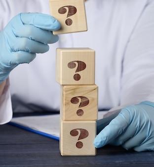 Cubo de madeira com um ponto de interrogação na mão do médico em uma superfície azul. o conceito de encontrar uma resposta para perguntas, métodos de tratamento