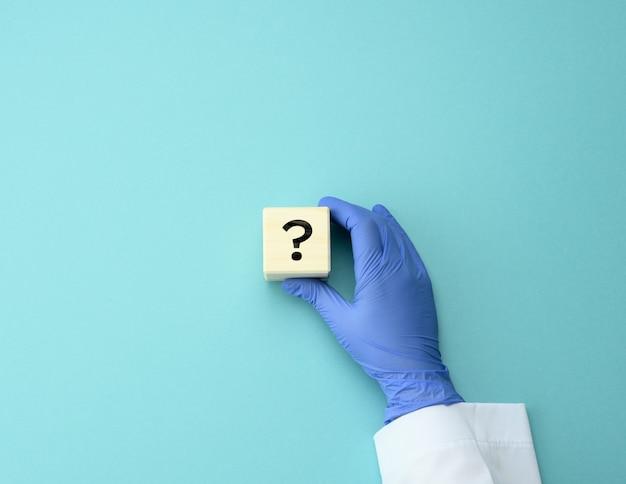 Cubo de madeira com um ponto de interrogação na mão do médico. o conceito de encontrar uma resposta para perguntas, métodos de tratamento