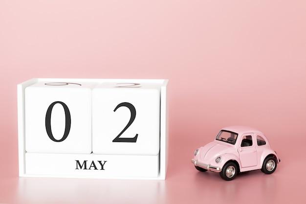 Cubo de madeira de close-up 2 de maio. dia 2 de maio mês, calendário em um fundo rosa com carro retrô.