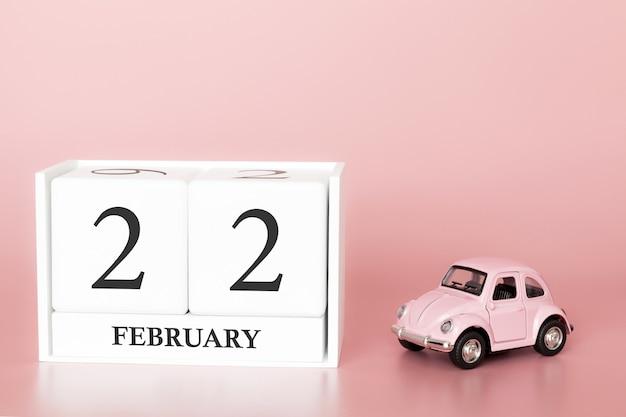 Cubo de madeira de close-up 22 de fevereiro. dia 22 do mês de fevereiro, calendário em um rosa com carro retrô.