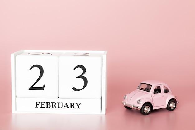 Cubo de madeira de close-up 23 de fevereiro. dia 23 do mês de fevereiro, calendário em um rosa com carro retrô.