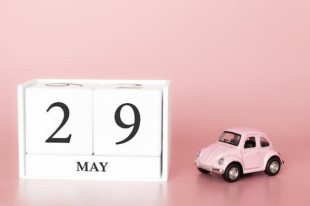 Cubo de madeira de close-up 29 de maio. dia 29 de maio mês, calendário em um fundo rosa com carro retrô.