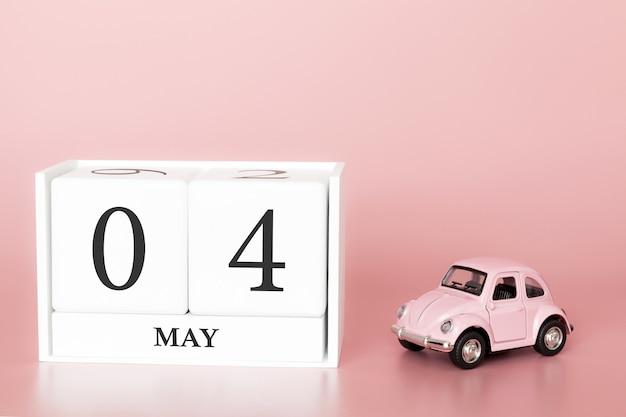Cubo de madeira de close-up 4 de maio. o dia 4 de pode mês, calendário em um fundo cor-de-rosa com carro retro.