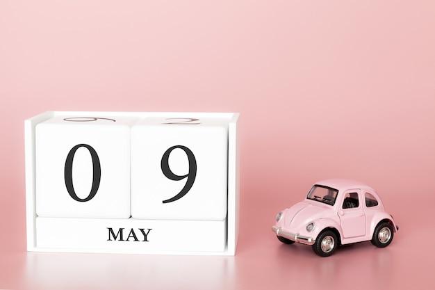 Cubo de madeira de close-up 9 de maio. dia 9 de maio mês, calendário em um fundo rosa com carro retrô.