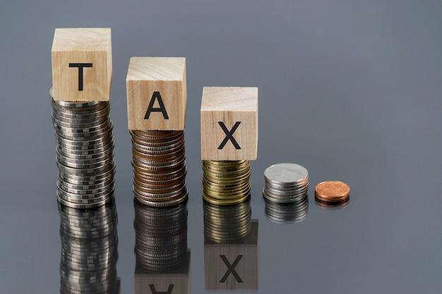 Cubo de madeira de imposto com pilha de moedas na mesa com refletor