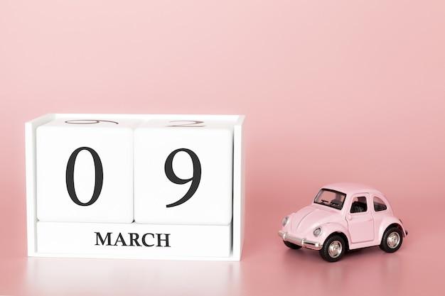 Cubo de madeira dia 9 de março. dia 9 do mês de março, calendário em um fundo rosa com carro retrô.