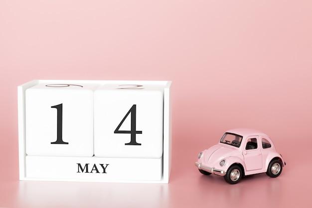 Cubo de madeira do close-up 14o maio. dia 14 de maio mês, calendário em um fundo rosa com carro retrô.