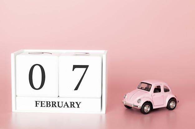 Cubo de madeira do close-up 7o fevereiro. dia 7 do mês de fevereiro, calendário em um rosa com carro retrô.