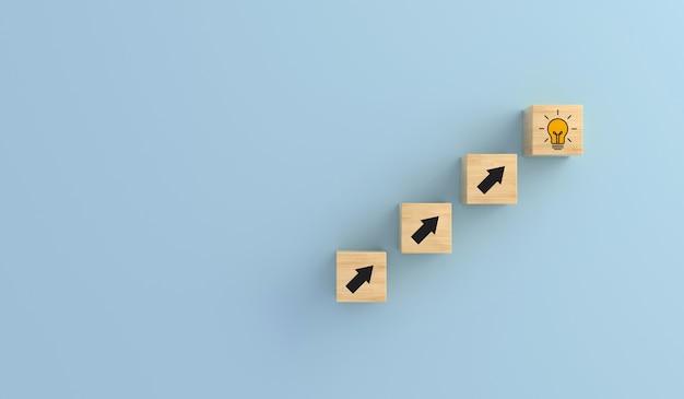 Cubo de madeira do ícone da lâmpada na escada de flechas. ideia criativa do conceito e inovação. renderização 3d.