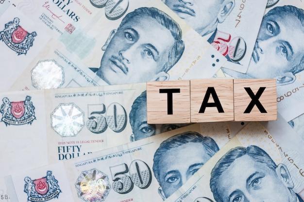 Cubo de madeira do imposto em cinquenta dólares de cingapura da nota de banco fundo.