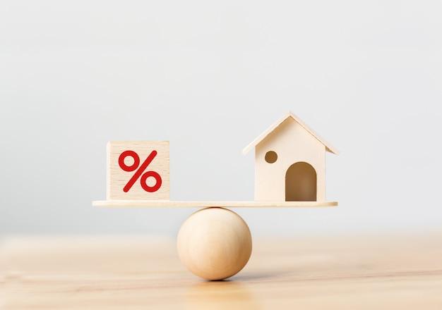 Cubo de madeira e casa forma de bloco com ícone por cento em escalas de madeira