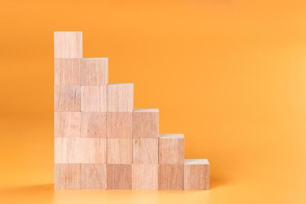 Cubo de madeira em branco simulado em forma de escada em fundo amarelo para criar uma carta ou símbolo, negócio, banner, conceito de publicidade.