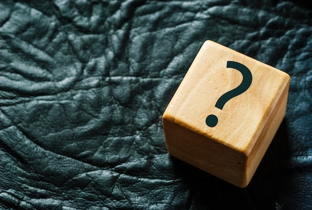 Cubo de madeira em couro preto com ponto de interrogação