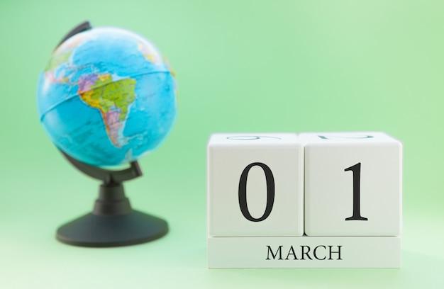 Cubo de madeira planejador com números, 1 dia do mês de março, primavera