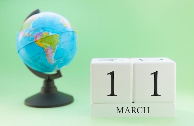 Cubo de madeira planejador com números, 11 dias do mês de março, primavera