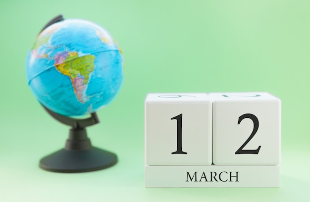 Cubo de madeira planejador com números, 12 dias do mês de março, primavera