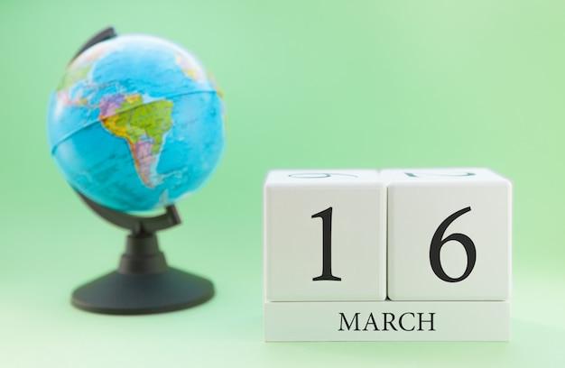 Cubo de madeira planejador com números, 16 dias do mês de março, primavera