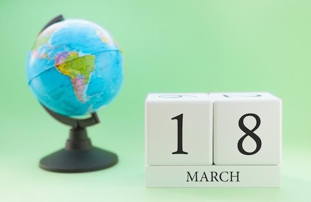 Cubo de madeira planejador com números, 18 dias do mês de março, primavera