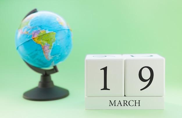 Cubo de madeira planejador com números, 19 dias do mês de março, primavera