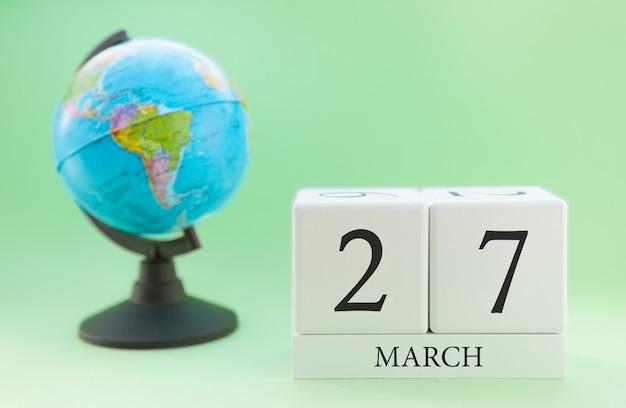 Cubo de madeira planejador com números, 27 dias do mês de março, primavera