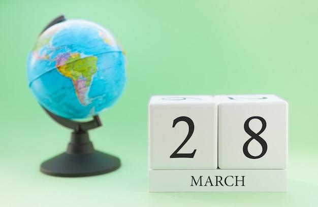 Cubo de madeira planejador com números, 28 dias do mês de março, primavera