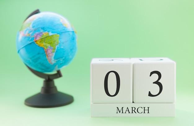 Cubo de madeira planejador com números, 3 dias do mês de março, primavera