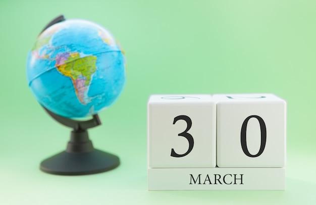 Cubo de madeira planejador com números, 30 dias do mês de março, primavera