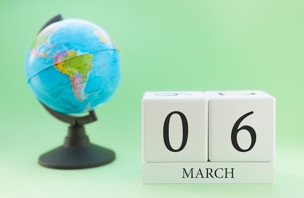 Cubo de madeira planejador com números, 6 dias do mês de março, primavera