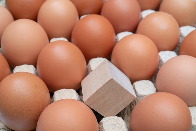 Cubo de madeira um entre ovos de galinha.