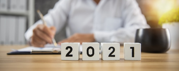 Cubo do ano número 2021 na mesa de madeira com um empresário trabalhando, escrevendo e verificando em papel comercial
