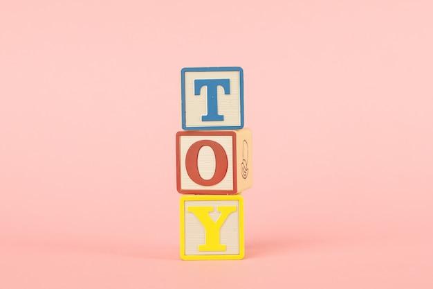 Cubos coloridos com letras com a inscrição brinquedo em um rosa