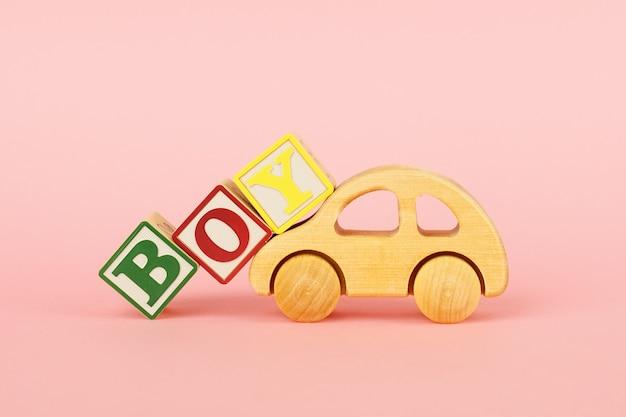 Cubos coloridos com letras menino e carro de brinquedo em um rosa