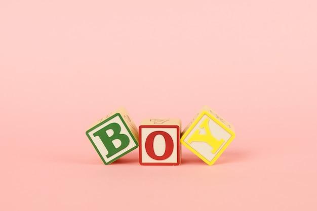 Cubos coloridos com letras menino em um rosa