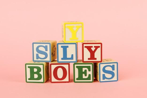 Cubos coloridos de brinquedo com letras em rosa