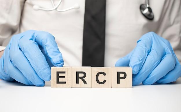 Cubos com a palavra ercp na mão do médico. conceito de cuidados.