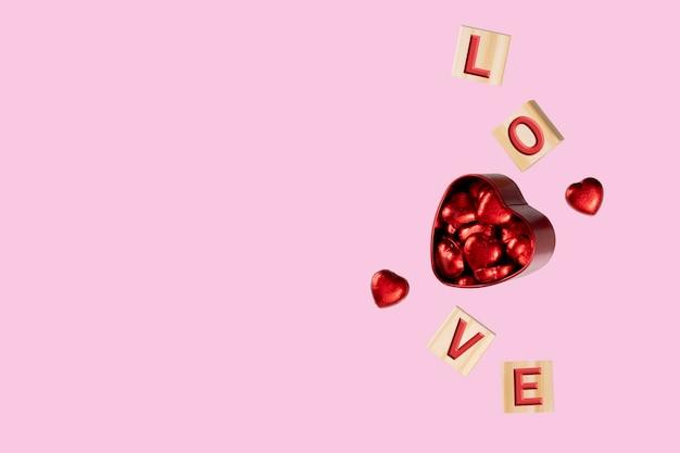 Cubos com as letras amor flutuando em torno de uma caixa de lata vermelha
