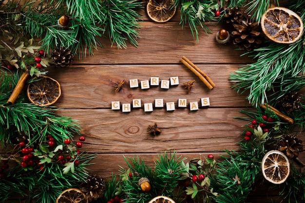 Cubos com letras perto de galhos de natal