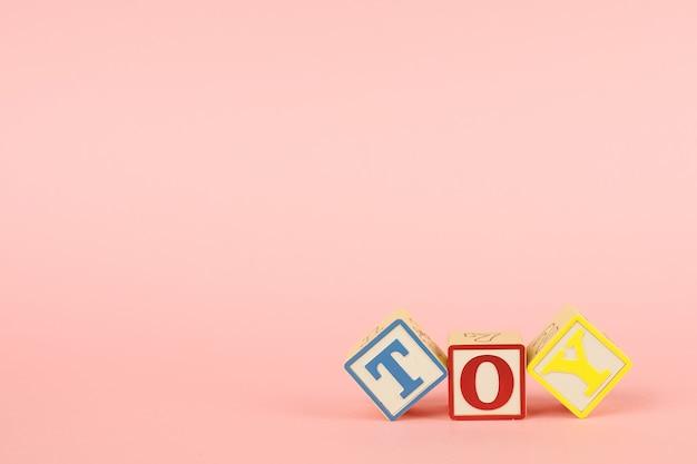 Cubos cor de rosa e coloridos com letras com a inscrição brinquedo