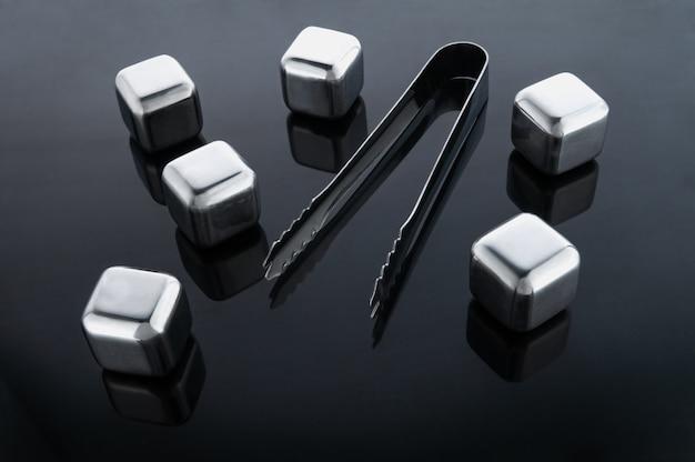 Cubos de aço simulando gelo para bebidas refrescantes. reutilizável. prateado. em uma superfície de espelho escura com reflexo. ao lado da pinça de dados.