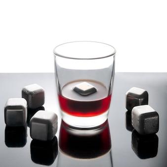 Cubos de aço simulando gelo para bebidas refrescantes. reutilizável. prateado. em uma superfície de espelho escura com reflexo. ao lado dos cubos está um copo de uísque.