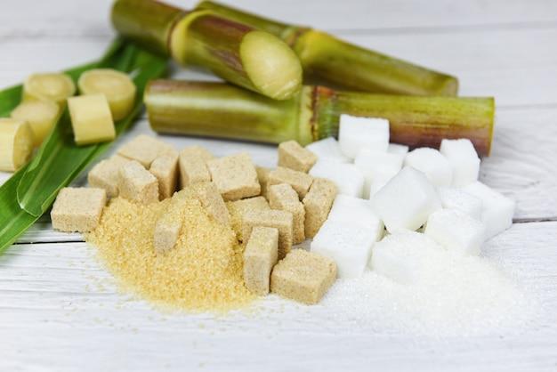 Cubos de açúcar branco e marrom e cana de açúcar na mesa de madeira
