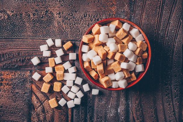 Cubos de açúcar branco e marrom em uma tigela laranja sobre uma mesa de madeira escura. vista do topo.