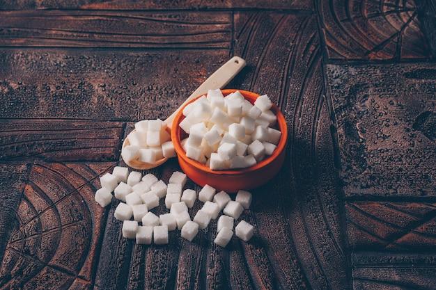 Cubos de açúcar branco em uma tigela laranja com vista de alto ângulo de colher em uma mesa de madeira escura