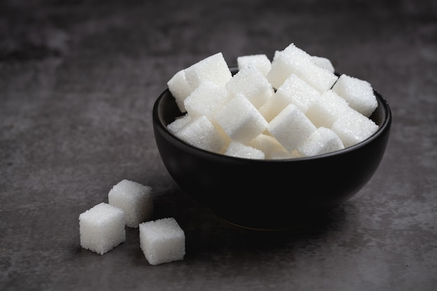 Cubos de açúcar branco em uma tigela na mesa.